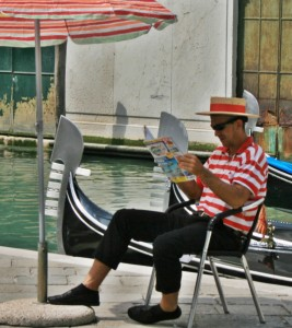 Off-Duty Gondolier Reading a Newspaper in Venice by a Gondola