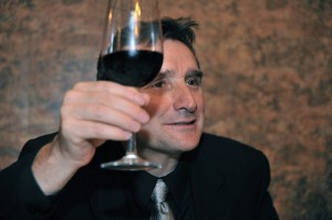 Toasting Traditions in France - Man raises a glass, must maintain eye contact
