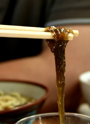 Okinawa seaweed hanging from chopsticks in Japan
