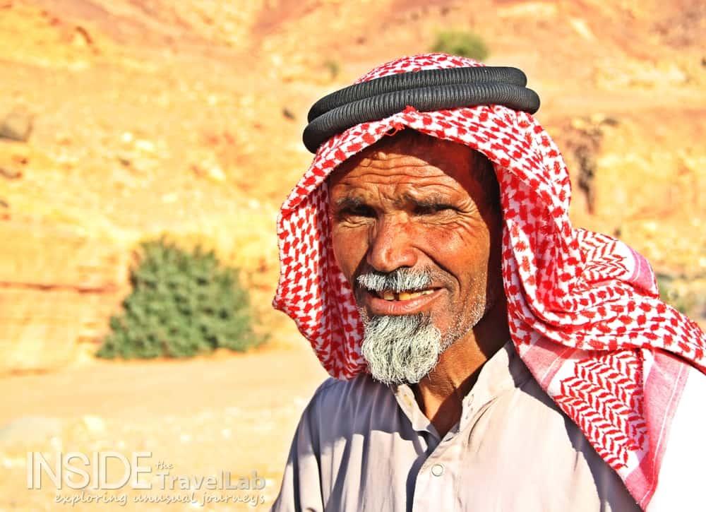 Man in traditional head dress in the desert in Jordan