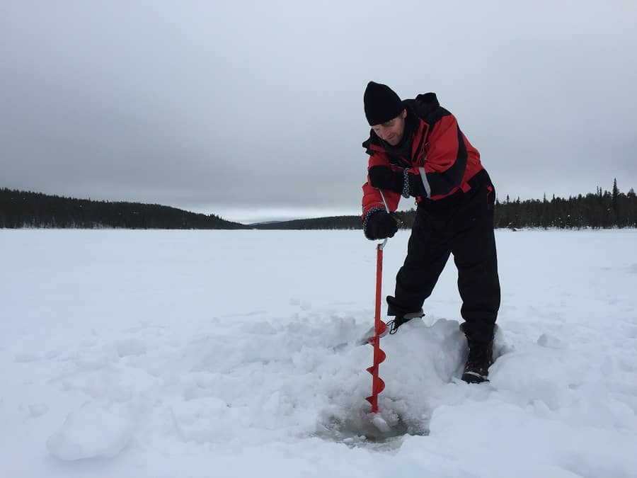 Sweden - Kiruna - Man carving hole in the ice for ice fishing