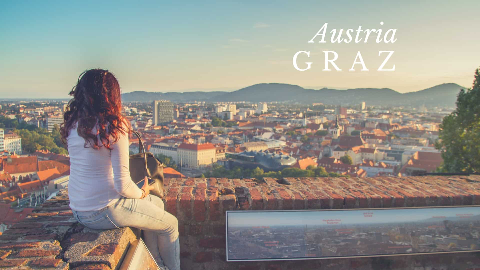 Austria Graz woman sits on Schlossberg overlooking the skyline of the city in summer