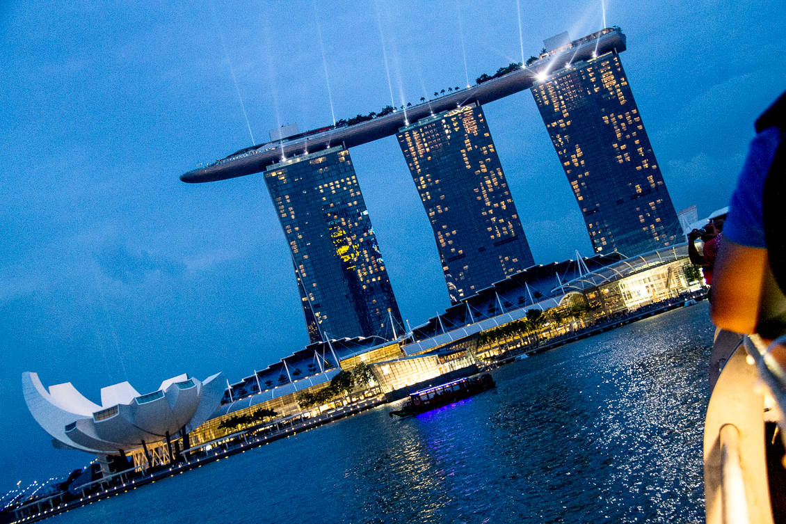 Singapore by night showing the battleship and flower from the river