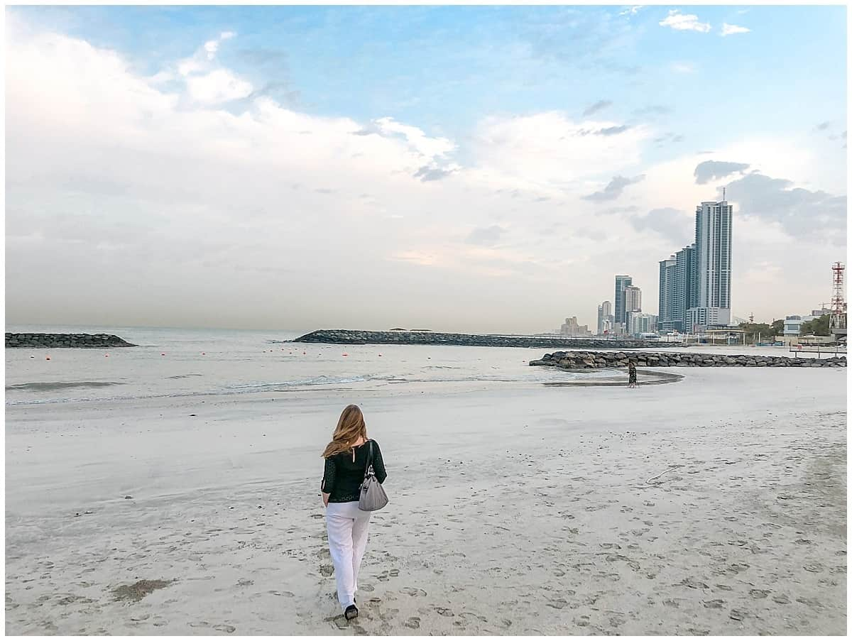 Woman walking on sand with Sharjah skyline in background
