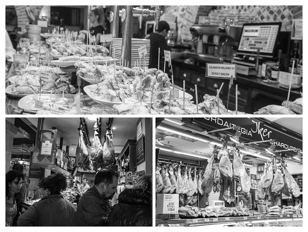 Black and white image of pintxos in San Sebastian including barside platters and hanging jamon