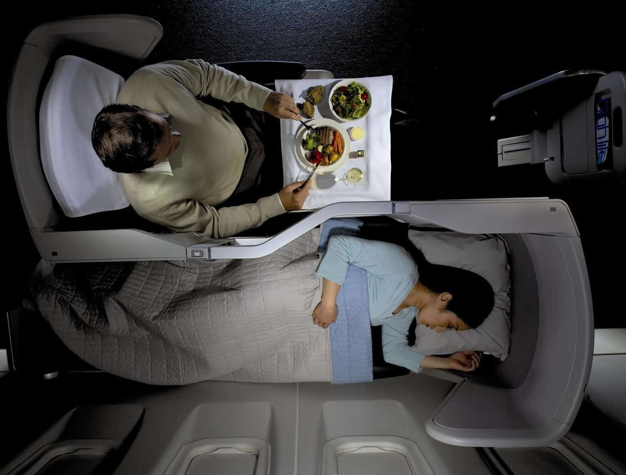 Overhead view of Club World British Airways Businsess Class with one passenger eating one sleeping