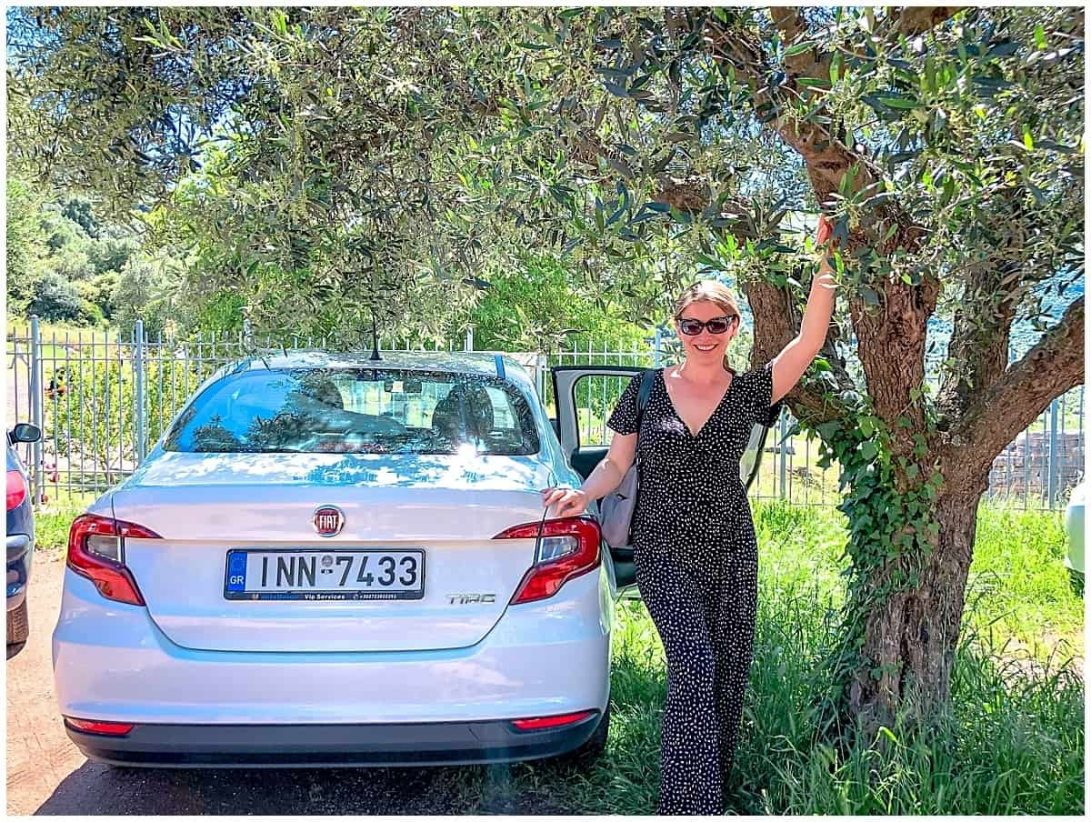 Abigail King standing by tree and car on a road trip in Greece