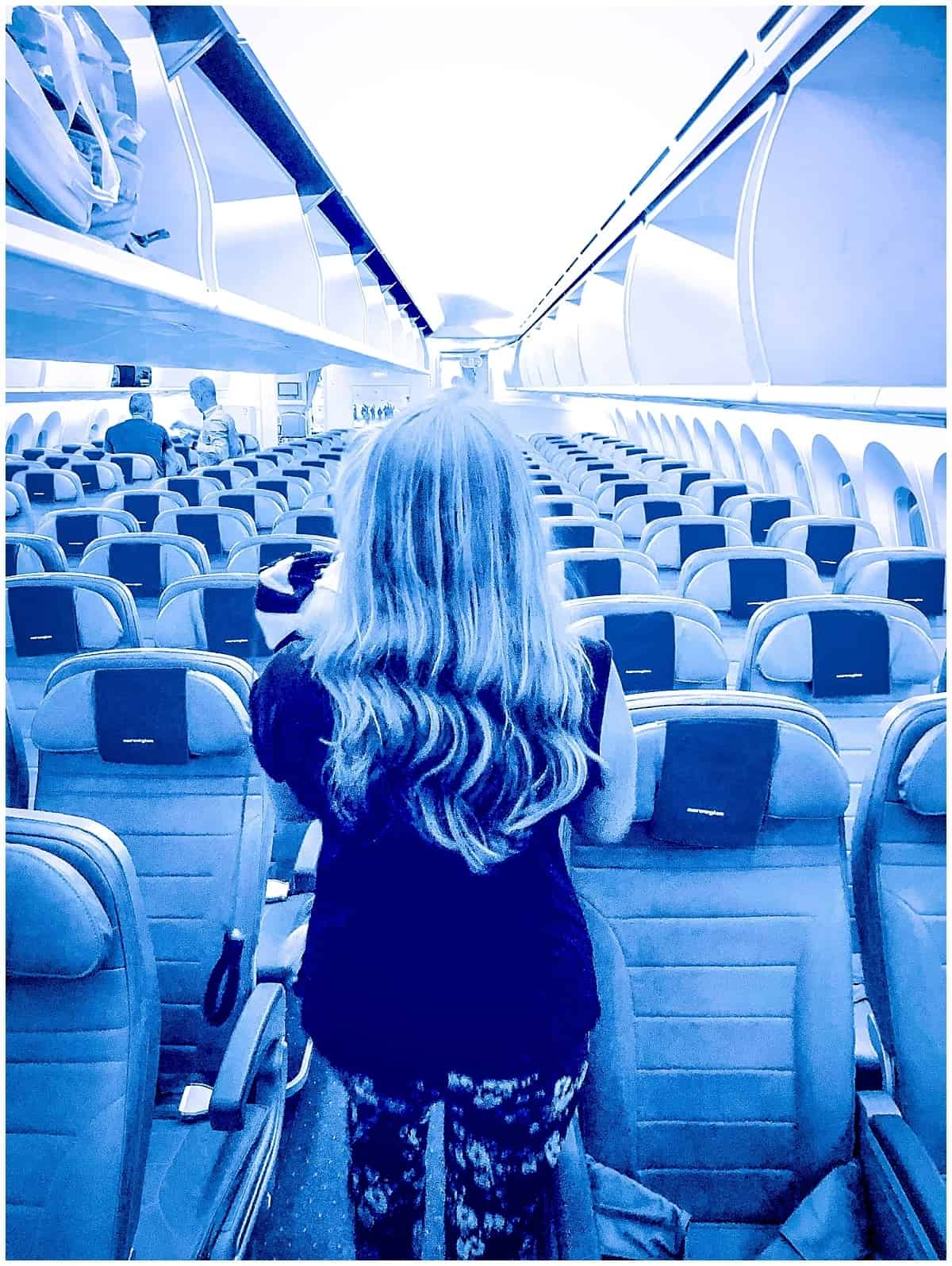 Abigail King walking along aeroplane aisle while boarding plane for a long haul flight