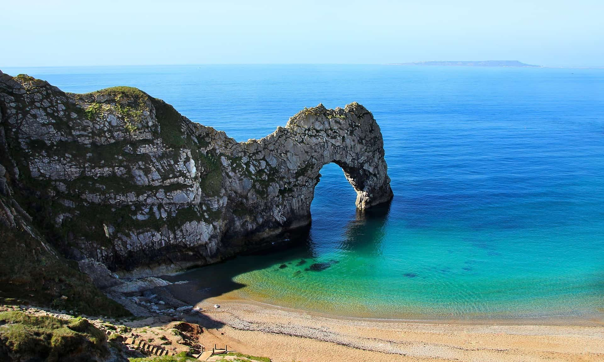 Stone arch of Durdledoor in Cornwall dips into the sea
