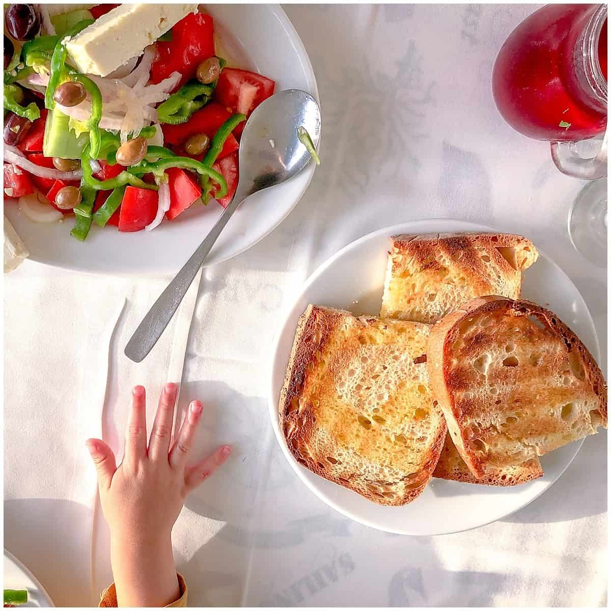 Toddler hand reaches for bread and Greek salad