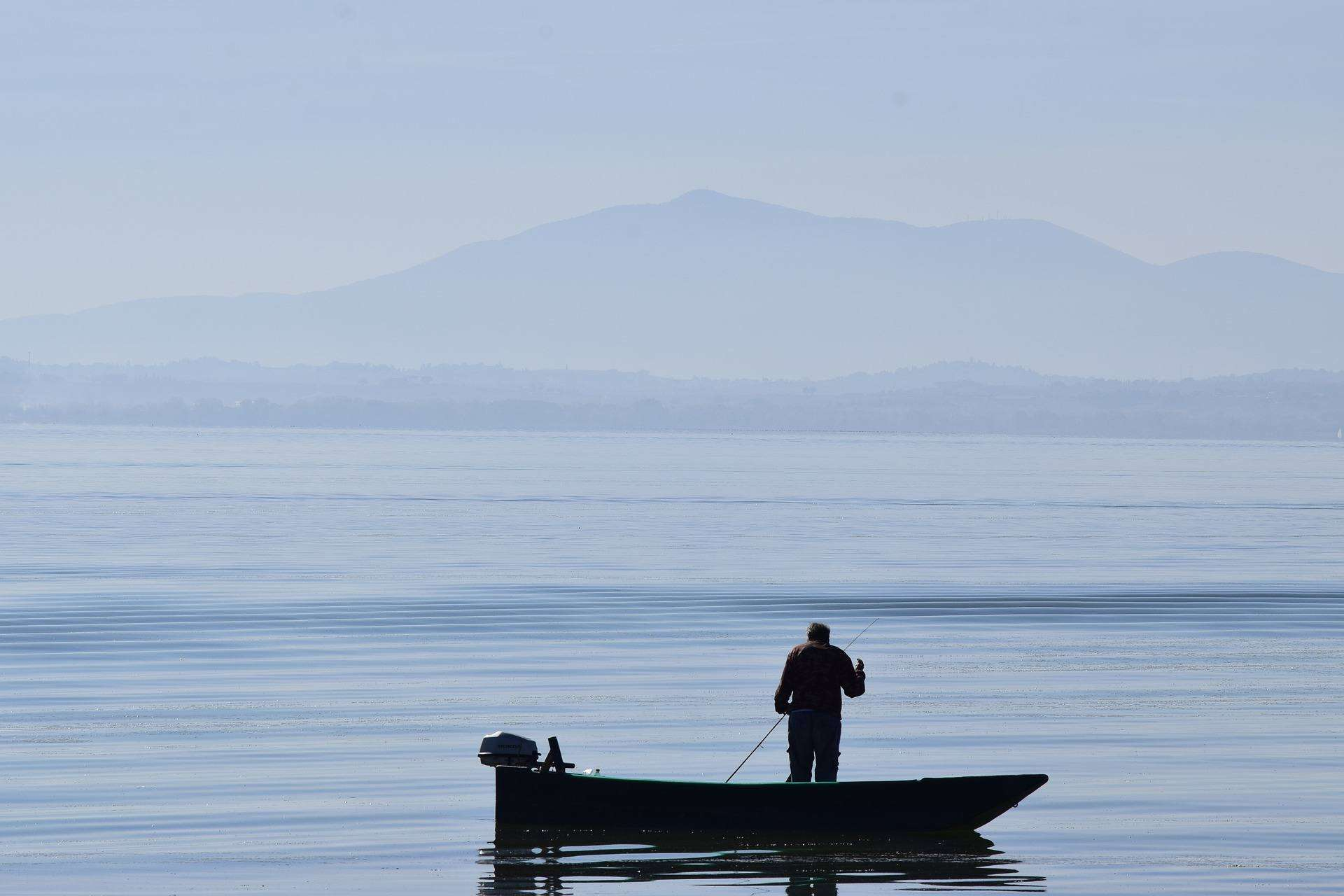 Lake Trasimeno in Umbria Italy person standing in boat with silhouette behind