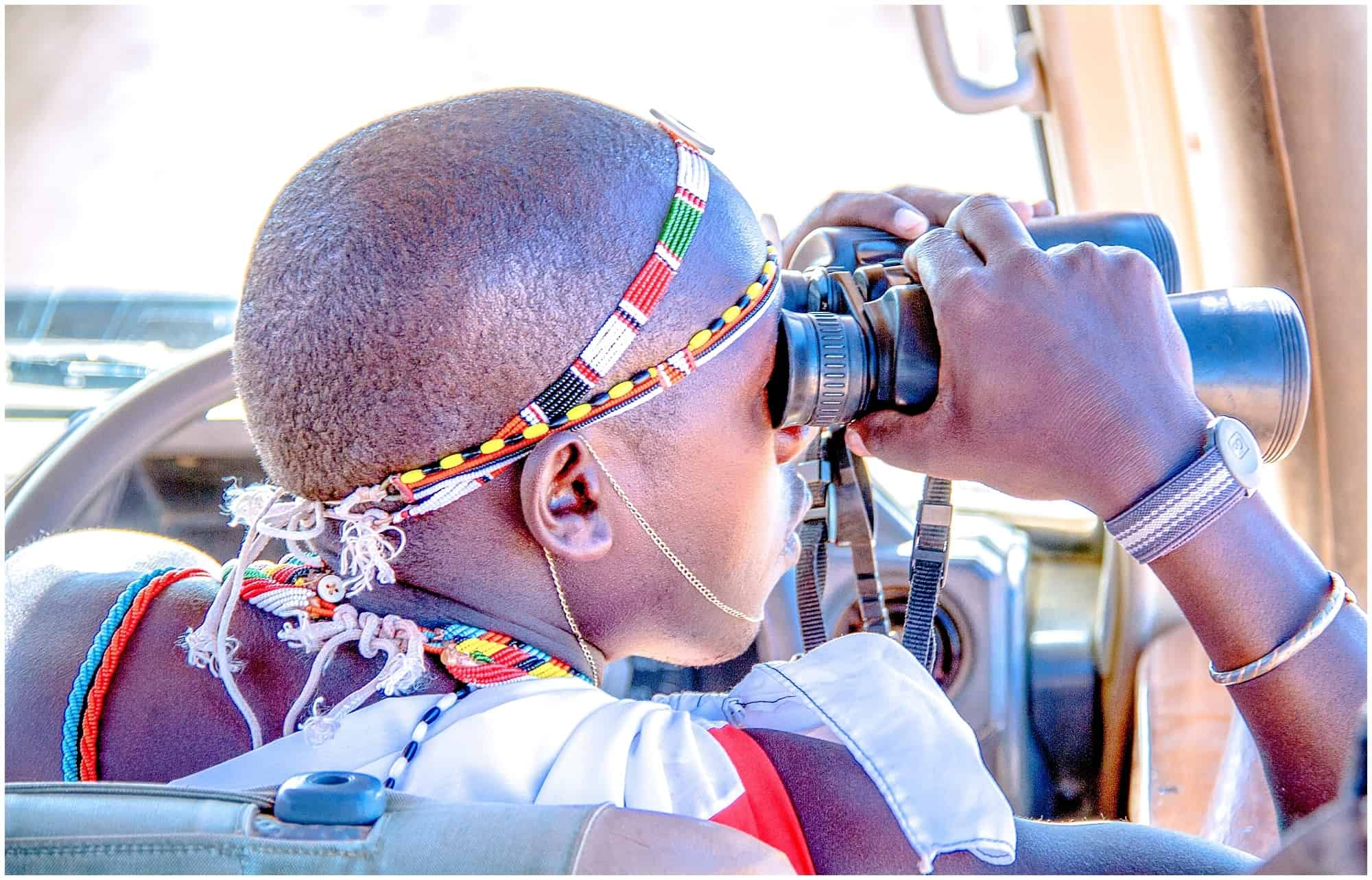 Safari guide in Kenya looking through binoculars