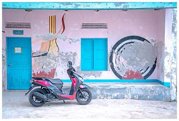 Red bike outside pink wall on Rinbudhoo Island in the Maldives