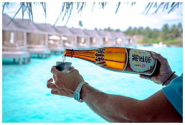 Pouring sake in the Maldives by the water bungalows