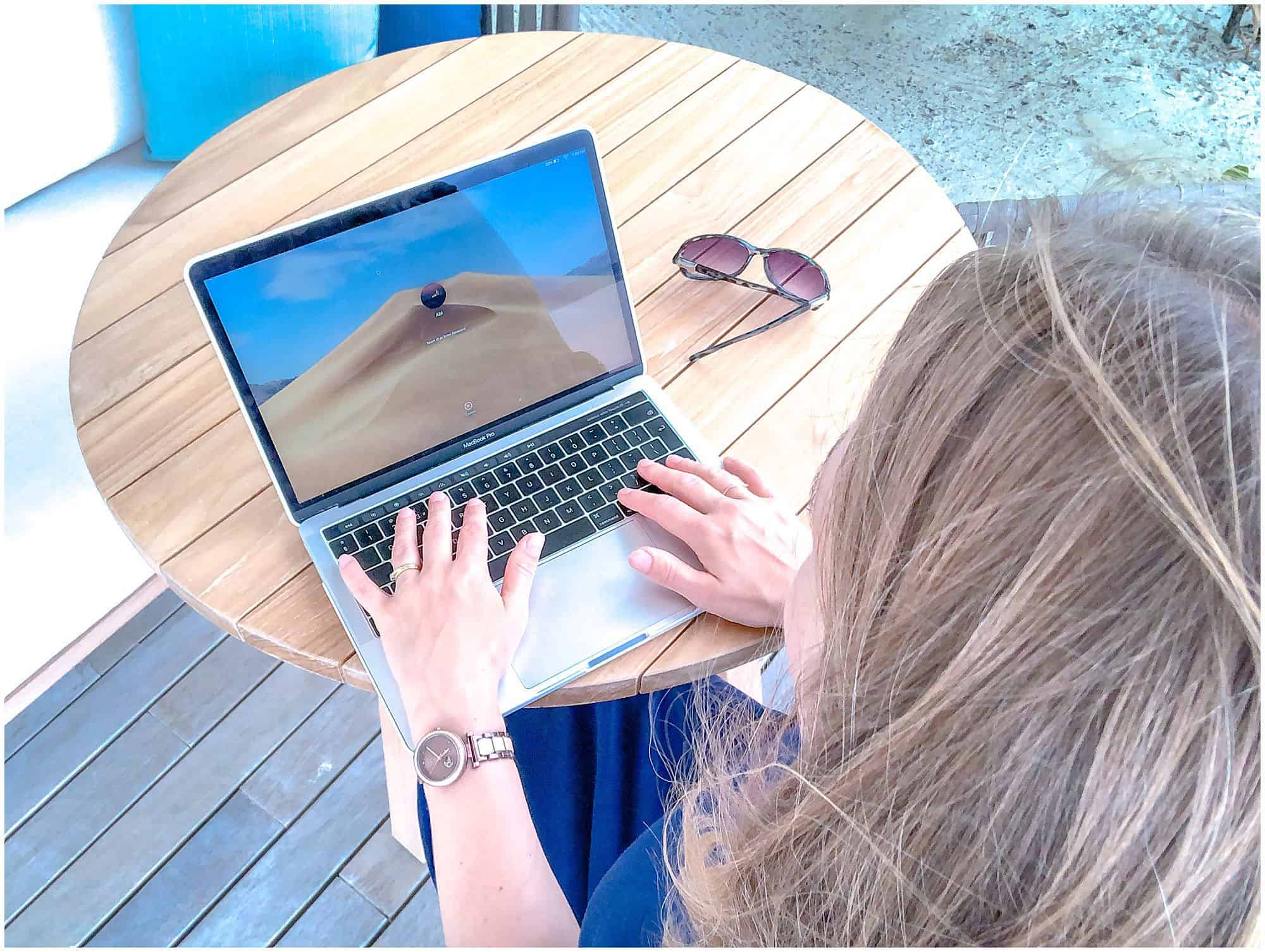 Woman working at laptop with sunglasses