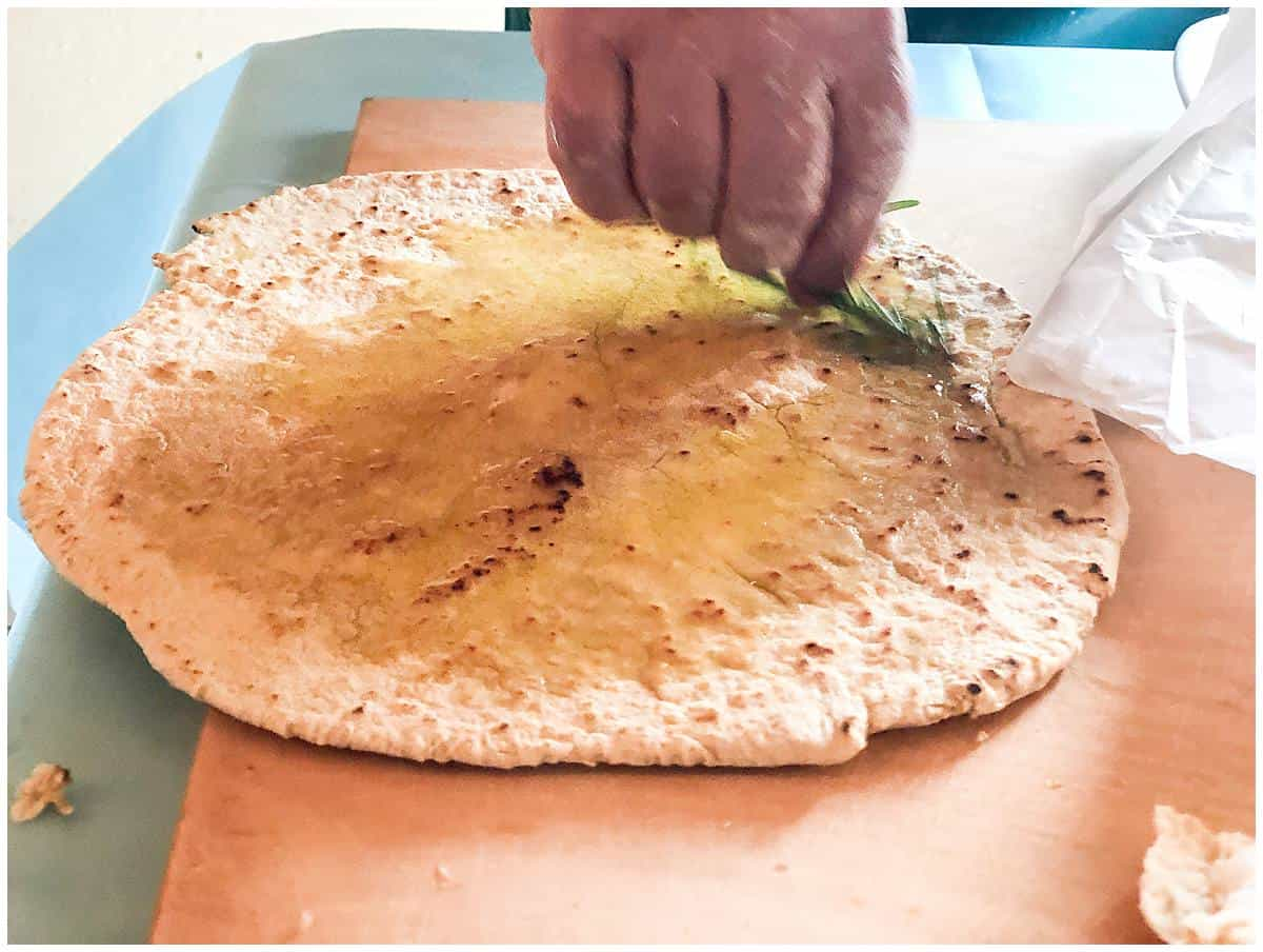 Making traditional flatbread piadina and drenching with olive oil and rosemary in a farm in San Marino