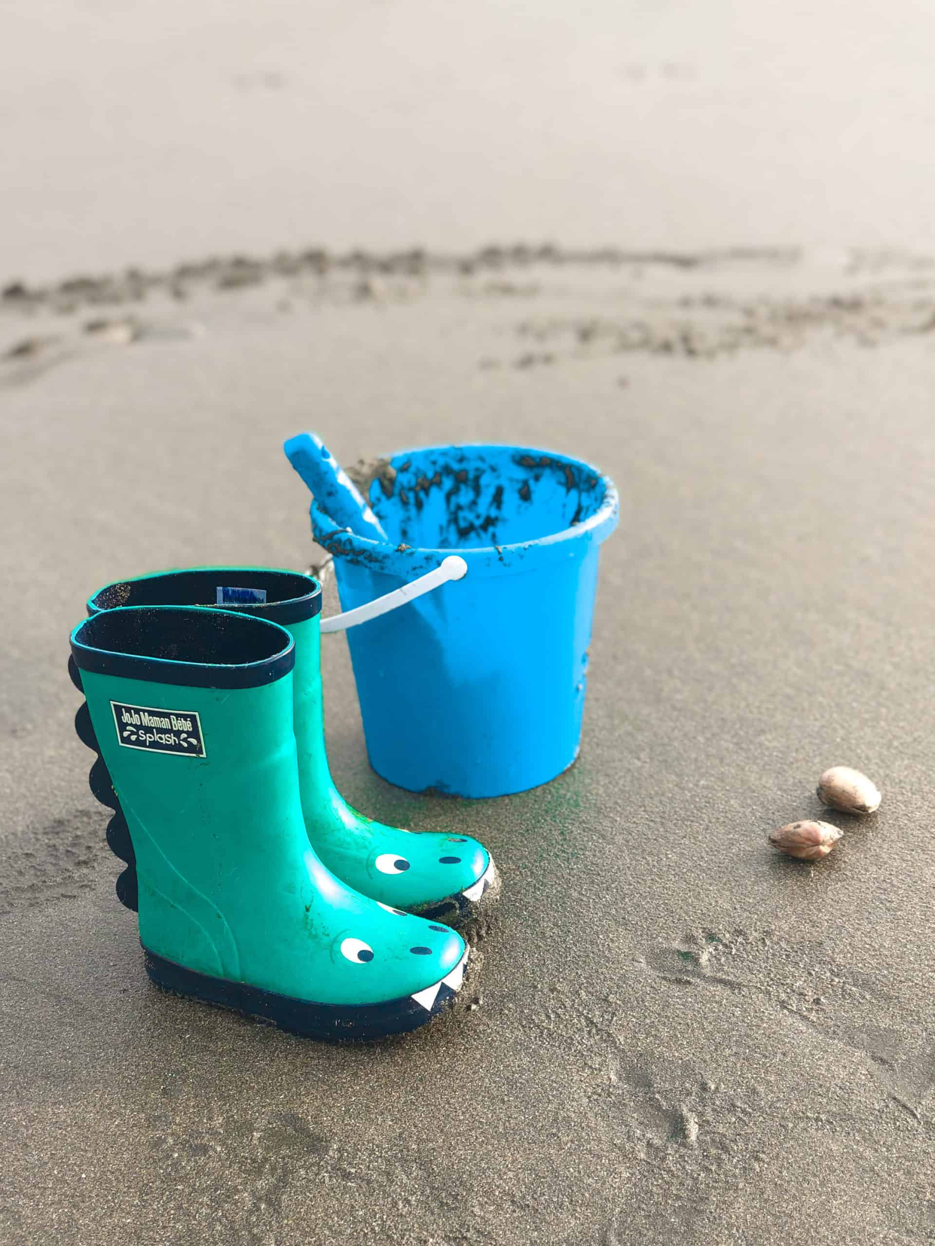 Summer Bucket List - wellies and bucket and spade on the beach with shells
