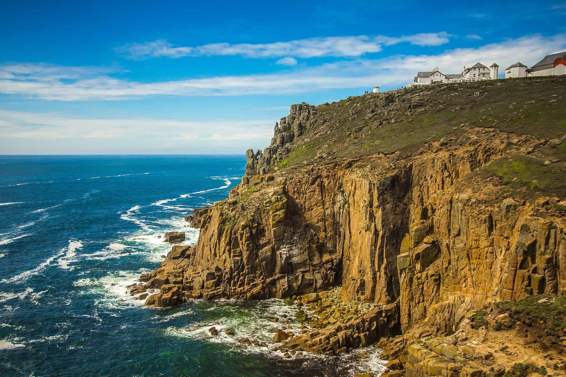 Prettiest places in Cornwall - Land's End clifftop and surf and buildings landscape