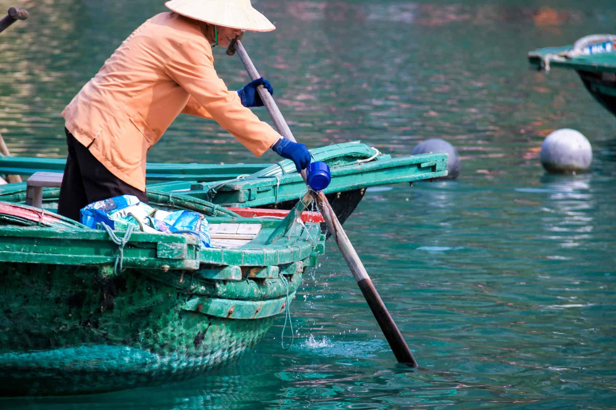 Vietnam - Halong Bay - Vung Vieng Floating Fishing Village Woman Rowing boat to gather tourists